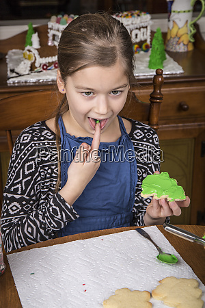 girl tasting the frosting from a