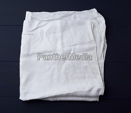 folded white linen towel on blue