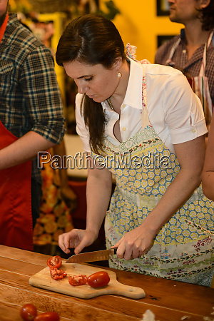 woman in apron chopping tomatoes large