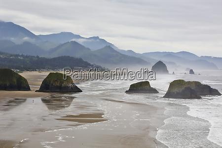 usa oregon cannon beach fog rises