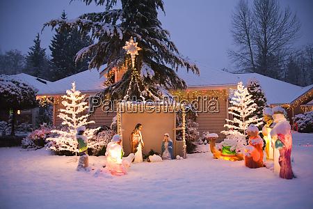home lit with christmas lights snow