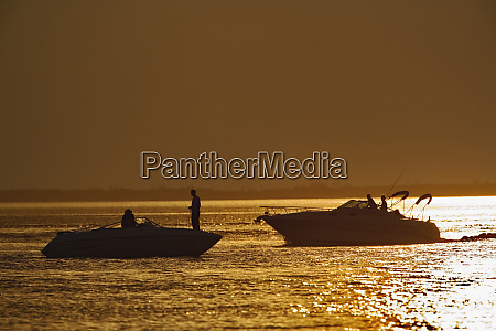 two recreational boats passing at sunset