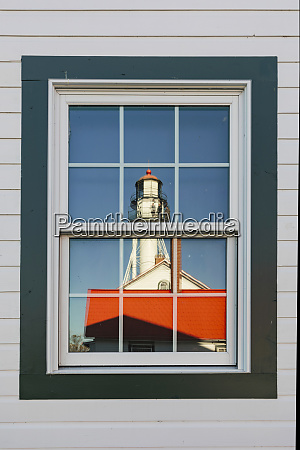 whitefish point lighthouse reflected in window