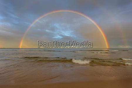 full arcing rainbow over lake michigan