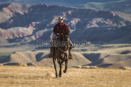 lone rider sauntering forward with badlands