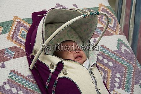 crying newborn infant bundled and wrapped