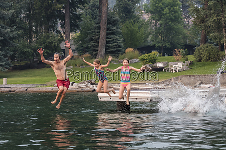 family jumping from dock into flathead