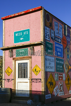 pink building covered in road signs