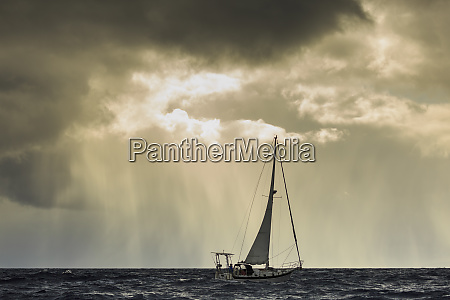 small sailboat in stormy seas near