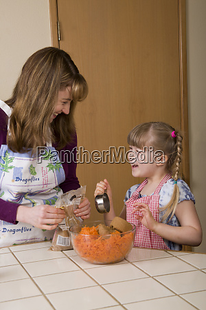 mother and daughter laughing while pouring