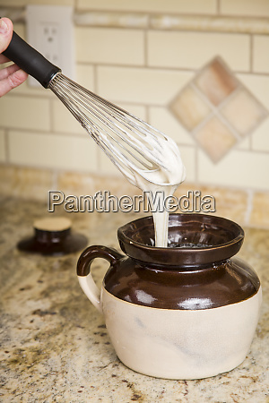 sourdough starter being stirred with a