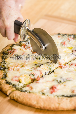 woman using a pizza cutter to