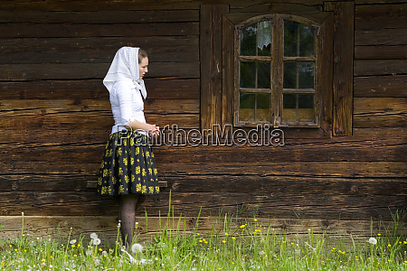 woman outside of full wooden church
