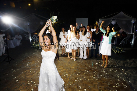 a bride throws her flowers into