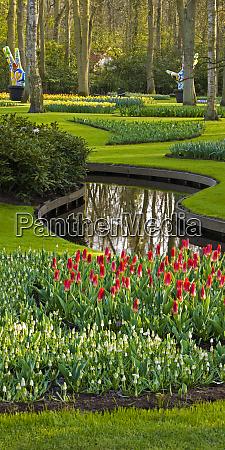 spring flowerbeds in formal woodland garden