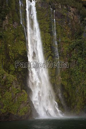 a tall waterfall drops off a