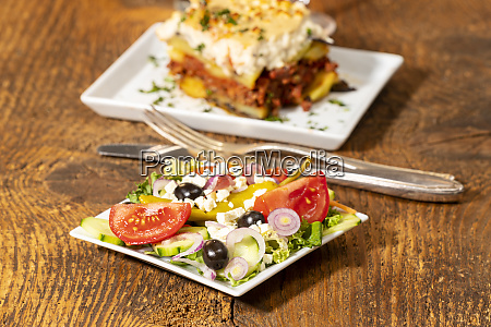 greek salad with moussaka on wood