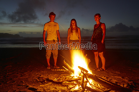 family around campfire on the beach