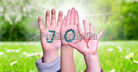 children hands building word joy grass