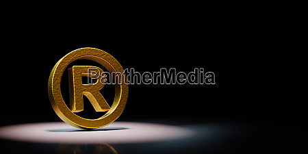 golden trademark symbol spotlighted on black