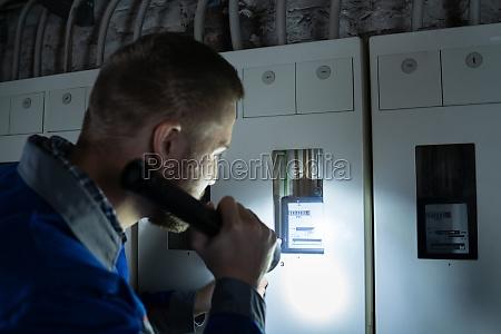 electrician examining a fusebox