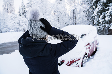shocked woman looking at car covered