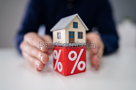 person protecting house model over cube