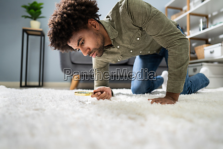 male looking at carpet with magnifying