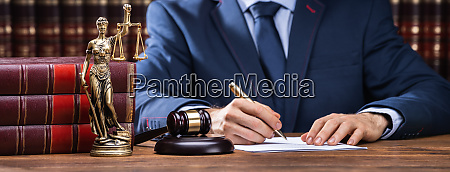 lawyer signing documents near mallet and