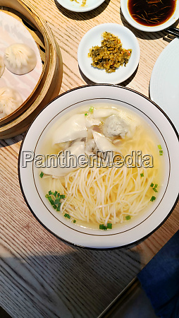 wontons in a broth with noodles