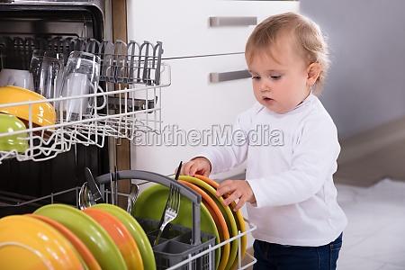 little girl unloading dishwasher