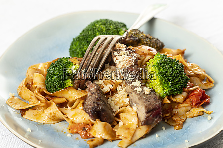 tagliatelli with steak slices on a