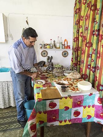 italy alberobello local gentleman chopping fresh
