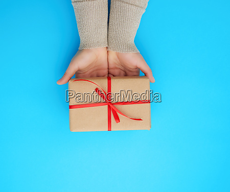 female hand holds a brown box