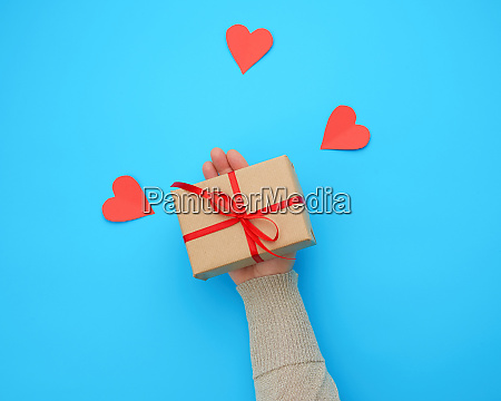 female hand holds a box wrapped