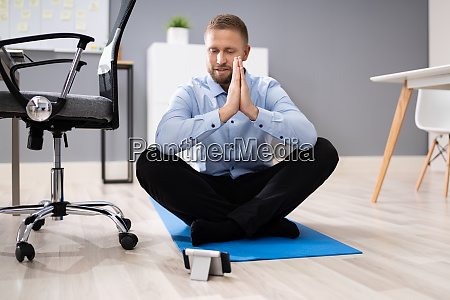 businessman meditating using smartphone app