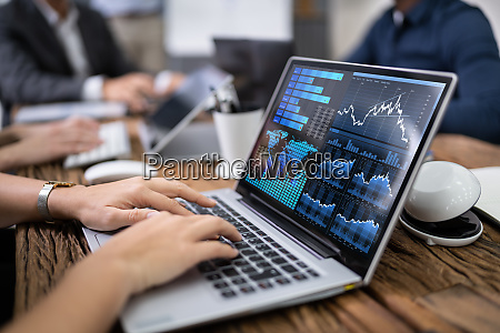 businessperson using laptop with graph on
