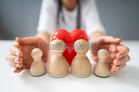 doctors hand protecting wooden pawn family