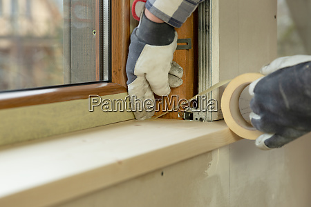 home improvement handyman installing window in