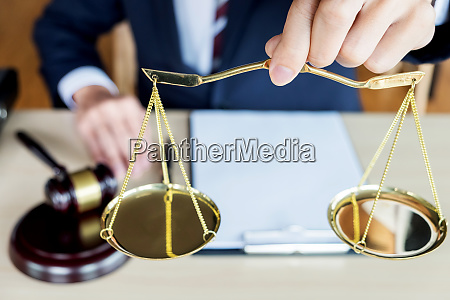 male judge holding golden weight