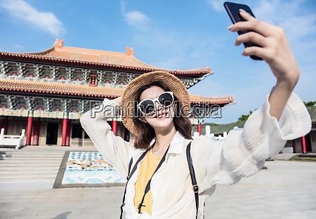 happy asian female traveler taking selfie