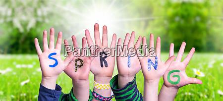 children hands building word spring grass