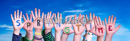 children hands building word springtime blue