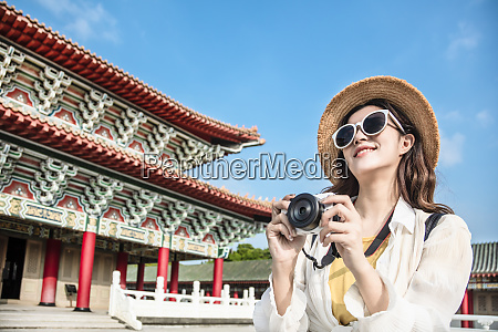 asian female traveler photographing temples at