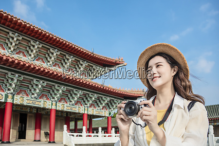 happy asian female traveler photographing temples