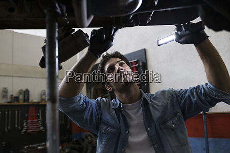 man in shirt standing under car