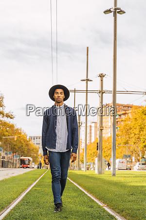 fashionable young man walking on tram