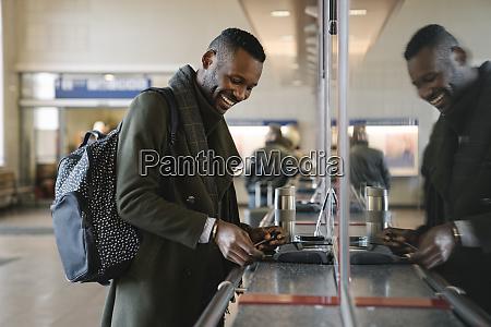 happy stylish man buying ticket in