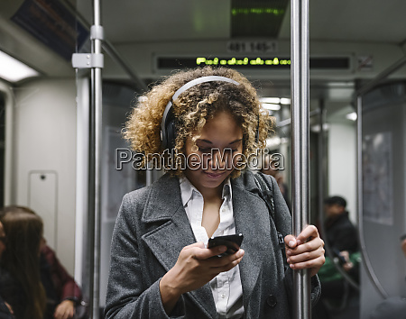 woman using smartphone on a subway