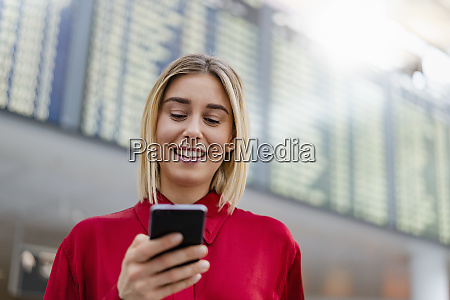 smiling young businesswoman using cell phone